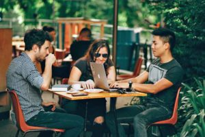 Tech Diversity (picture depicts a woman and two men sitting at an outdoor table at a coffee shop)