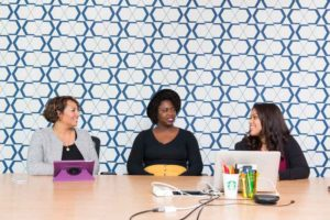 Women in Tech (picture shows a blue wallpaper background, with three women of color sitting at a table with laptops)