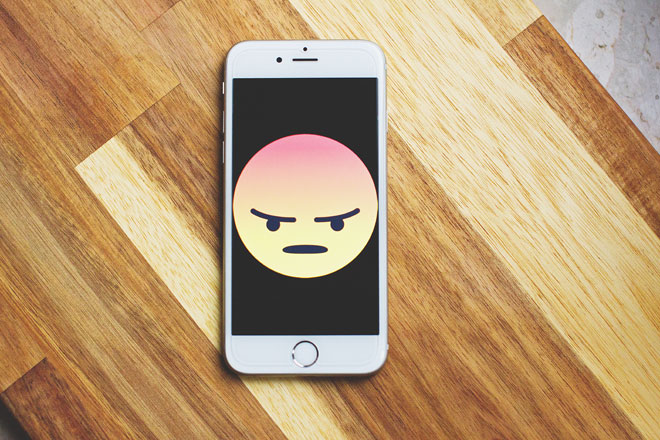 An iPhone on a table with a screen depicting an angry cartoon face to represent bad user experience
