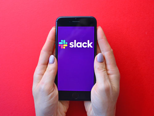 Slack Workplace Boundaries (two hands holding a mobile phone with the Slack app open)